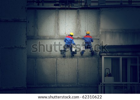 Painters in hard hats and harnesses hanging high on concrete wall, working. - stock photo