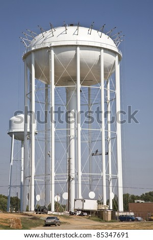 Painters painting giant water tower to complete the construction of this new city water reservoir