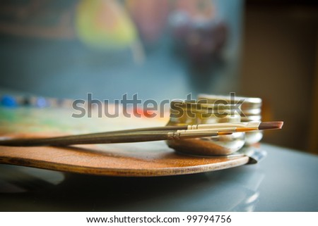 Painters palette. Wooden painter's palette with three artists paint brushes and steel twin dippers close-up on background of still-life painting in art studio interior. - stock photo