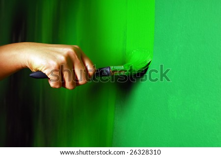 Painting a wall with paint brush in green - stock photo