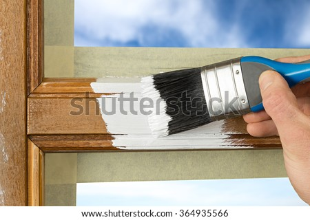 painting a window frame with white color - stock photo