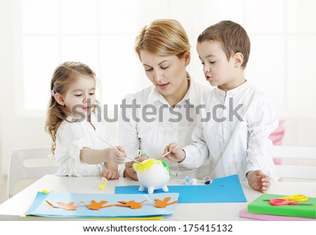 Painting activity with teacher - stock photo
