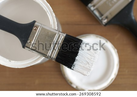Painting and decorating shallow focus top down view of a pot of white paint and brush - stock photo