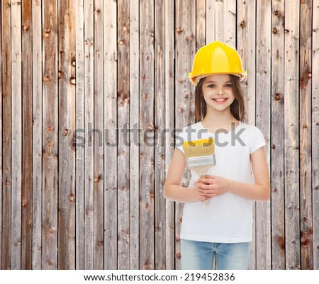 painting, building, childhood and people concept - smiling little girl in protective helmet with paint brush over wooden fence background - stock photo