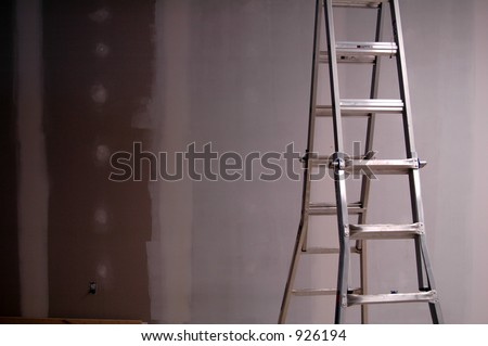 Painting drywall using ladder - stock photo