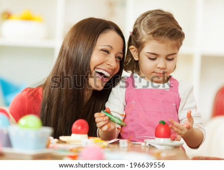 Painting Easter eggs is fun! - stock photo