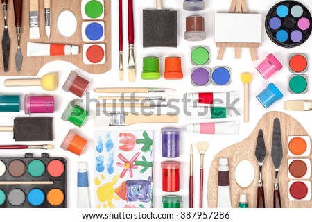 painting equipment: brushes, palette and paints on white background. multicolored flat lay composition top view - stock photo