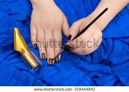 Painting fingers with dark blue nails on bright blue tissue background - stock photo