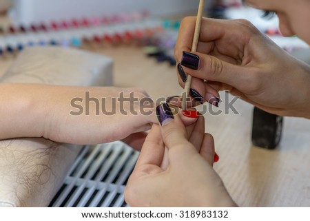 painting nails in nail salon, UV lap of quick dry nail polish manicure, focus on corrective stick - stock photo
