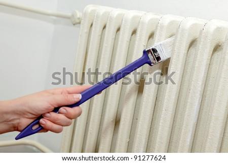 Painting of retro white radiator with brush - stock photo