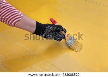 Painting of wooden floor, workers hand and brush