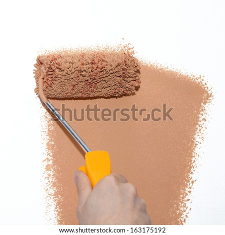 Painting roller on white wall with brown paint - stock photo