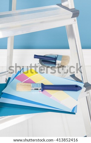 Painting the interior with tins and brushes on stepladder - stock photo