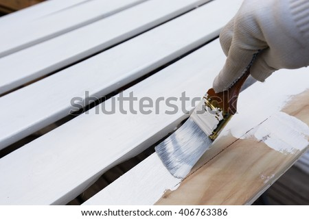 Painting timber boards with the white paint - stock photo