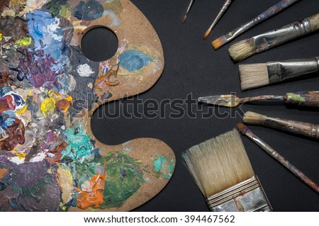 Painting utensils/Abstract view of some used painting utensils such as a color mixing palette, a few brushes in a variety of strokes and a palette knife, all covered in multi colored paint. - stock photo