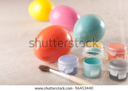 Painting vibrant colorful eggs for Easter holiday