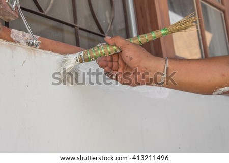 Painting walls.Painter paints using a brush,hand worker holding brush painting white on cement wall, and soft-focus background (select focus hand hold brush) - stock photo