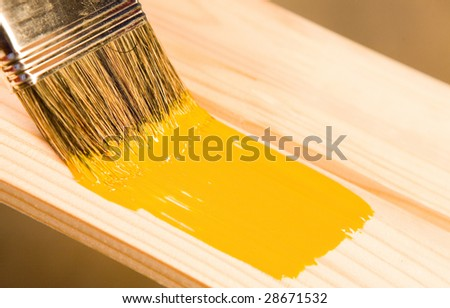Painting wooden detail with yellow color - stock photo