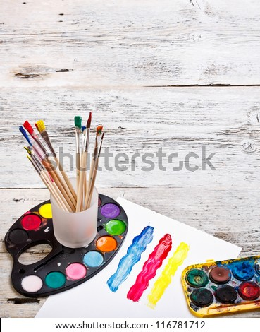 Paints and brushes on a wooden background - stock photo