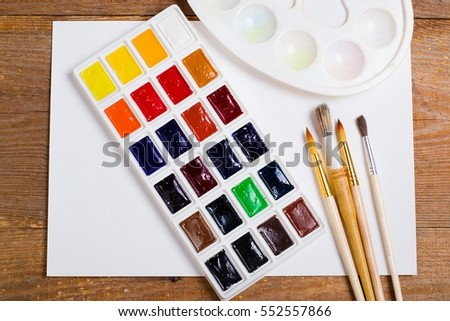 Paints, brushes and album - drawing tools on a desk
