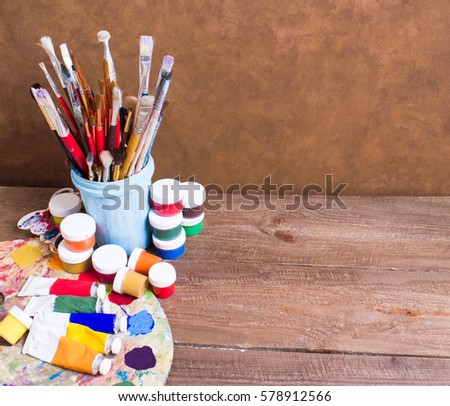 Paints, brushes and palette on the brown wooden background. The workplace of the artist. Banner for school
