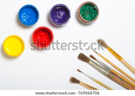 paints in jars and a brush on a white sheet of paper, top view