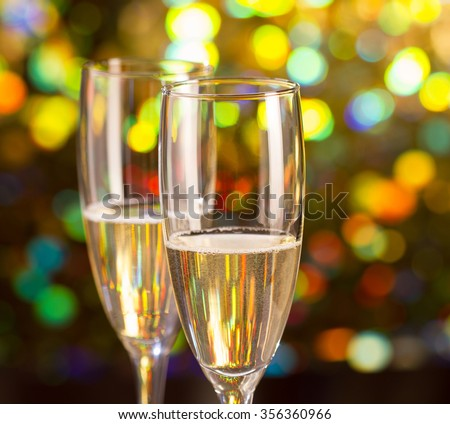 Pair glass of champagne and champagne bottle on bokeh background - stock photo
