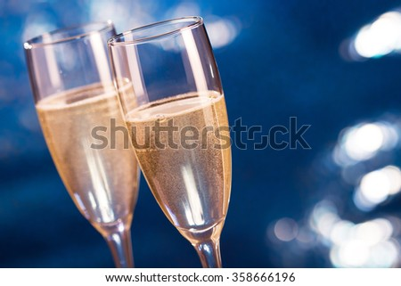 Pair glass of champagne on blue bokeh background - stock photo