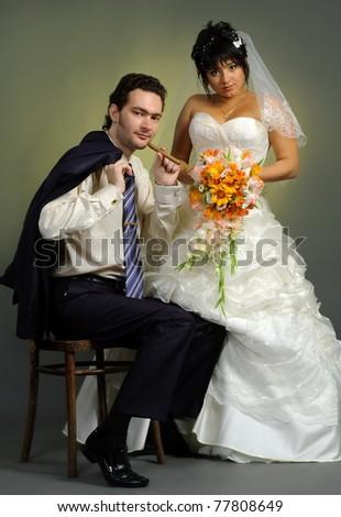 Pair newlyweds bridegroom and bride pose in studio - stock photo