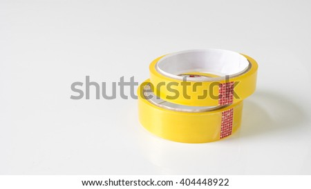 Pair of a transparent, moisture proof adhesive material cellophane tape. Isolated on empty background. Slightly de-focused and close-up shot. Copy space. - stock photo