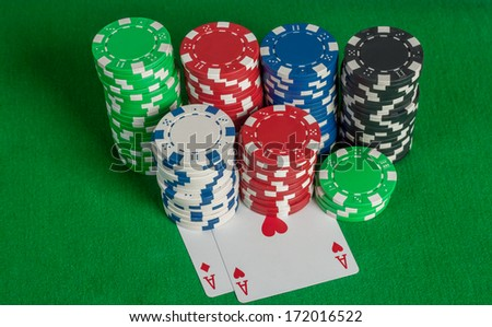 pair of aces and poker chips stack on green table - stock photo