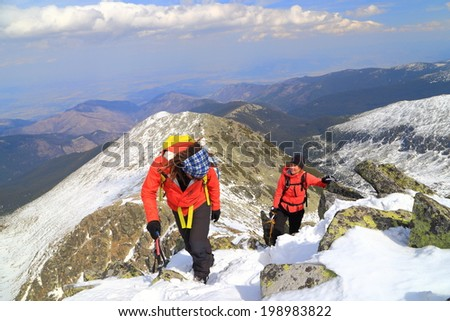 Pair of alpine climbers ascend on the mountain in winter - stock photo