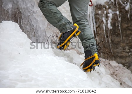 Pair of alpinist boots in crampons on ice - stock photo