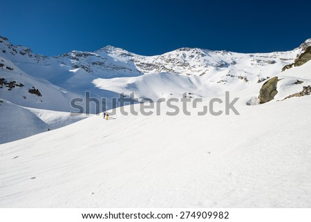 Pair of alpinist hiking uphill by ski touring on snowy slope towards the mountain summit in a bright sunny day of spring. Concept of conquering adversities and reaching the goal. Italian Alps. - stock photo