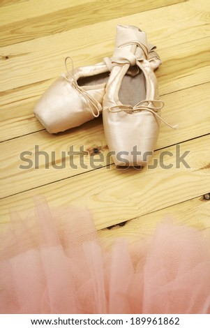 pair of ballet shoes pointes with ribbons on wooden floor