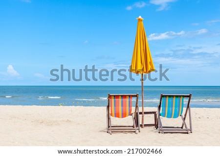 Pair of beach chair with sun umbrella on beautiful beach. Concept for rest, relaxation and holiday. - stock photo