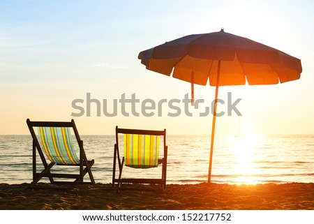 Pair of beach loungers on deserted coast sea at sunrise - stock photo