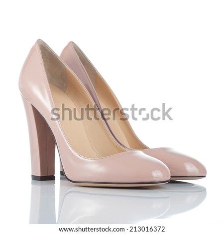 pair of beige varnished leather female high heel shoes. isolated on white