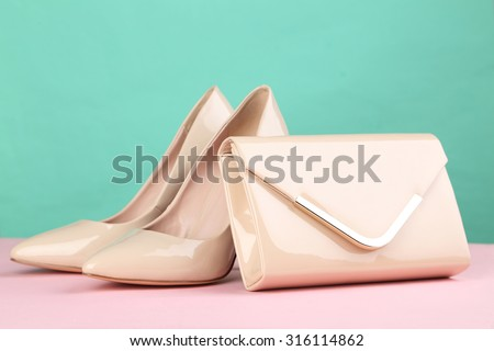 Pair of beige women's high-heeled shoes with handbag on a pink background - stock photo