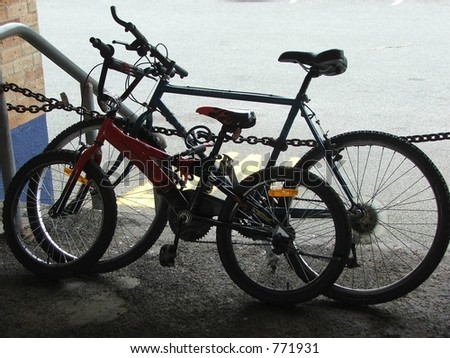 pair of bicycles chained to bars - stock photo