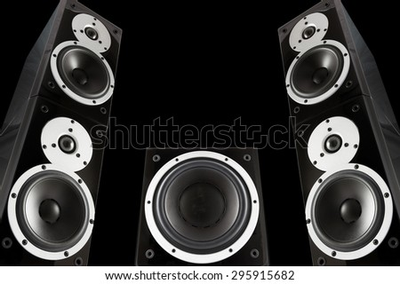 Pair of black music speakers and subwoofer isolated on black background