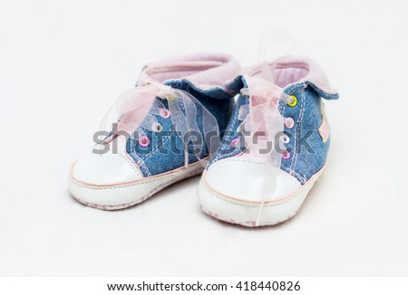 Pair of blue and white baby shoes, not isolated - stock photo