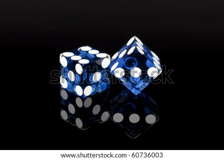 Pair of blue casino gaming/gambling dice isolated on a black background with reflection. - stock photo