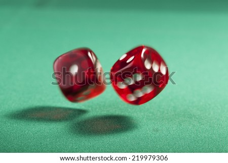 Pair of bouncing red dice blured on green  background  - stock photo