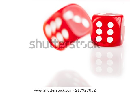 Pair of bouncing red dice isolated on white background with reflection - stock photo