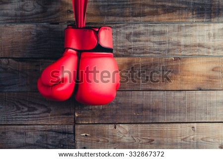 Pair of boxing gloves hanging in a rustic wooden wall. Vintage filter. - stock photo