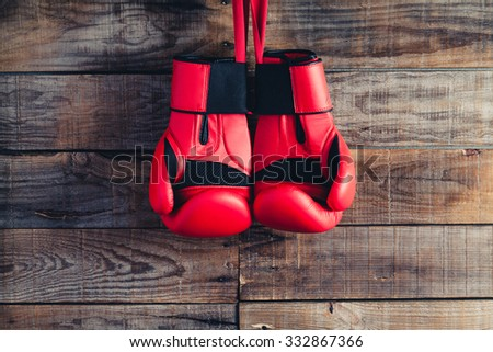 Pair of boxing gloves hanging in a rustic wooden wall. Vintage tone. - stock photo