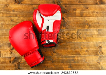 Pair of boxing gloves on wooden planks background - stock photo