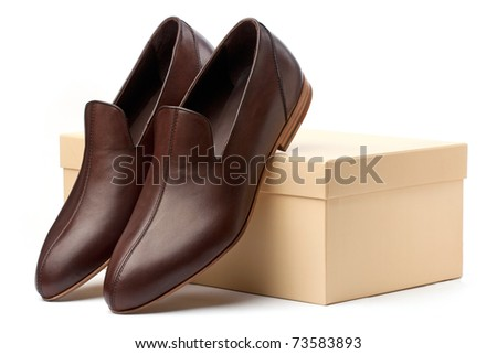 Pair of brown male shoes in front of sale box on white - stock photo