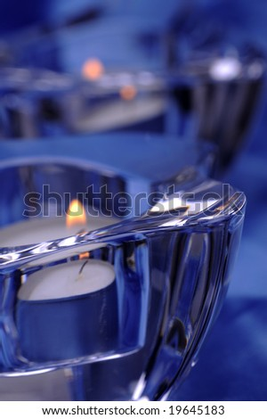 Pair of candles in a glass candlesticks, blue silk background